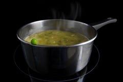 Verse groene erwt op een pot met het stomen van groentesoep op een indu stock fotografie