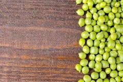 verse groene erwten op een bruin houten close-up als achtergrond met een plaats voor een inschrijving Hoogste mening stock afbeelding