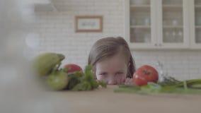 Verse groentecourgette, tomaten en greens die op de lijst leggen Het leuke meisje kijkt van de lijst, het verbergen stock videobeelden