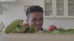 Verse groentecourgette, tomaten en greens die op de lijst leggen De positieve Afrikaanse Amerikaanse man kijkt van stock videobeelden
