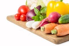 Verse groenten bij houten scherpe raad op wit Stock Afbeeldingen