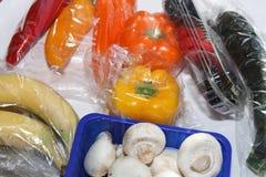 Verse groenten en vruchten in plastiek stock foto's