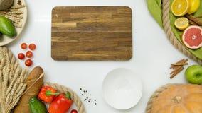 Verse groenten, fruit, houten scherpe raad op witte achtergrond Royalty-vrije Stock Foto