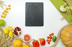 Verse groenten, fruit, zwarte scherpe raad op witte achtergrond, hoogste mening Stock Fotografie