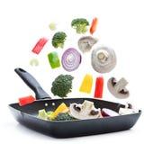 Verse groenten klaar voor koken die in een grillpan vliegen die op wit wordt geïsoleerd stock foto's