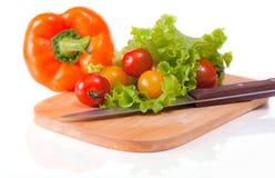 Verse groenten op een hakbord en een mes Stock Afbeeldingen
