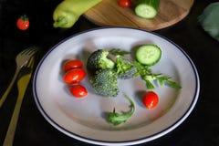 Verse groenten op witte plaat Broccoli gesneden komkommers en kers/druiventomaten stock foto