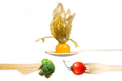 Verse groententomaat, broccoli, physalis op houten vork, mes, lepel Stock Foto's