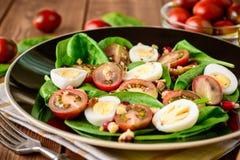 Verse groentesalade met spinazie, kersentomaten, kwartelseieren, granaatappelzaden en okkernoten in zwarte plaat op houten lijst Royalty-vrije Stock Afbeeldingen