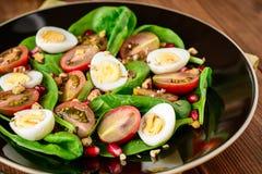 Verse groentesalade met spinazie, kersentomaten, kwartelseieren, granaatappelzaden en okkernoten in zwarte plaat op houten lijst Stock Foto's