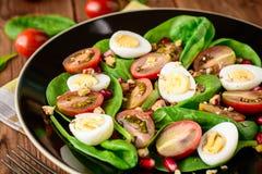 Verse groentesalade met spinazie, kersentomaten, kwartelseieren, granaatappelzaden en okkernoten in zwarte plaat op houten lijst Stock Fotografie