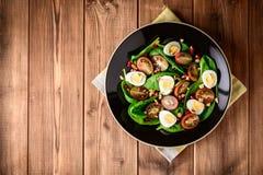 Verse groentesalade met spinazie, kersentomaten, kwartelseieren, granaatappelzaden en okkernoten in zwarte plaat op houten lijst Stock Foto