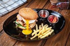 Verse hamburger met kippenei, sla en saus op een zwarte plaat met frieten Amerikaans snel voedsel Chickenburger met exemplaar stock foto