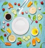 Verse heerlijke salade en het kleden zich ingrediënten rond lege witte plaat op lichtblauwe achtergrond, hoogste mening, kader Ge Stock Afbeelding