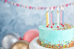 Verse heerlijke verjaardagscake met kaarsen dichtbij ballons op kleurenachtergrond stock foto