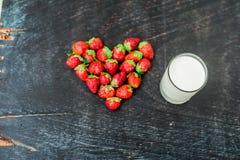Verse het hartvorm van de aardbeienserie en een glas melk op oude houten achtergrond Stock Fotografie