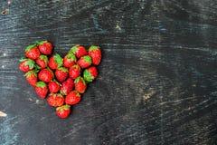 Verse het hartvorm van de aardbeienserie op oude houten achtergrond Royalty-vrije Stock Afbeeldingen