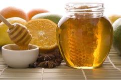 Verse honing met honingraat, kruiden en vruchten Royalty-vrije Stock Foto's