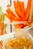 Verse hummusonderdompeling met ruwe wortel en selderie Stock Afbeeldingen