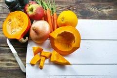 Verse ingrediënten voor pompoen soep met appel, sinaasappel, wortel Royalty-vrije Stock Afbeeldingen