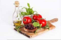 Verse ingrediënten voor salade: tomaten, zwarte olijven, raket, bas Stock Afbeeldingen