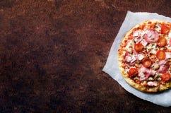 Verse Italiaanse pizza met paddestoelen, ham, tomaten, kaas bij de steun van document, donkere achtergrond De ruimte van het exem Royalty-vrije Stock Afbeelding
