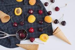 Verse kersen, abrikozen en wafelkegel op geruit servet royalty-vrije stock foto