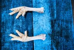 Verse kippenvoeten op een achtergrond van blauwe raad Achtergrond FO stock afbeeldingen