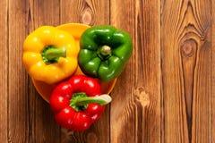 Verse kleurrijke groene paprika's met druppels op houten lijst stock foto