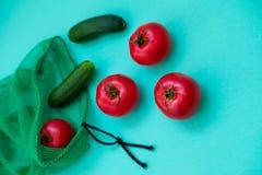 Verse komkommers en tomaten die van netto winkelen uitvallen stock foto