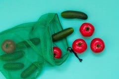 Verse komkommers en tomaten die van netto winkelen uitvallen stock fotografie