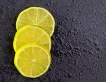 Verse lima plakken met waterdalingen op zwarte Stock Foto's