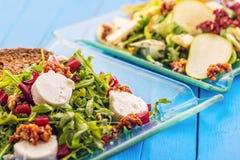 Verse mengelings plantaardige salades op glasplaat op blauwe houten achtergrond, productfotografie voor restaurant of gezonde lev Royalty-vrije Stock Afbeeldingen