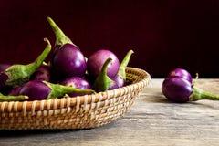 Verse mini purpere aubergine in de mand op houten achtergrond Stock Foto's