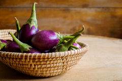 Verse mini purpere aubergine in de mand op houten achtergrond Stock Foto