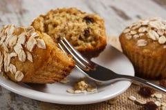 Verse muffins met havermeel dat met volkorenbloem op witte plaat, heerlijk gezond dessert wordt gebakken Stock Foto
