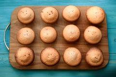Verse muffins op een scherpe raad op een houten blauwe achtergrond bedelaars Stock Fotografie