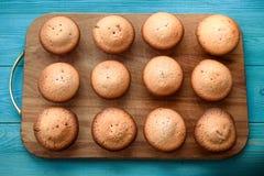Verse muffins op een scherpe raad op een houten blauwe achtergrond bedelaars Royalty-vrije Stock Foto's
