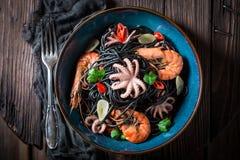 Verse nad smakelijke spaghetti met zeevruchten met garnalen en octopus stock fotografie
