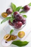 Verse natte pruimen met bladeren in de kom op vin Royalty-vrije Stock Foto's