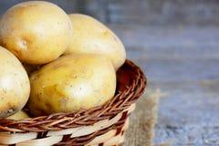 Verse nieuwe aardappels Ruwe nieuwe aardappel in een rieten mand op een uitstekende houten lijst close-up Royalty-vrije Stock Afbeeldingen