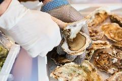Verse oester gehouden met in hand mes open Stock Afbeelding