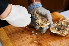 Verse oester gehouden met in hand mes open Royalty-vrije Stock Foto's