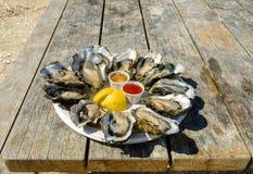 Verse oesters in een witte plaat met ijs en citroen op een houten bureau Royalty-vrije Stock Foto's
