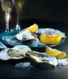 Verse oestersclose-up op blauwe plaat, gediende lijst met oesters, citroen in restaurant Royalty-vrije Stock Foto