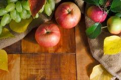 Verse oogst van appelen Aardthema met groene druiven en appel op houten achtergrond Het concept van het aardfruit stock foto