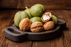 Verse oogst van okkernoten op een houten achtergrond Groene en bruine noten op een mooie houten plaat Shell en schil van okkernot Stock Afbeeldingen
