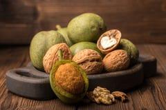Verse oogst van okkernoten op een houten achtergrond Groene en bruine noten op een mooie houten plaat Shell en schil van okkernot Stock Fotografie