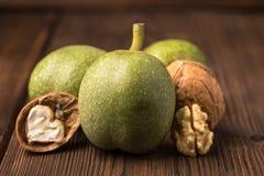 Verse oogst van okkernoten op een houten achtergrond Groene en bruine noten Shell en schil van okkernoten Royalty-vrije Stock Afbeelding