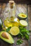 Verse organische avocado, kalk, peterselie en olijfolie op oud hout Royalty-vrije Stock Fotografie